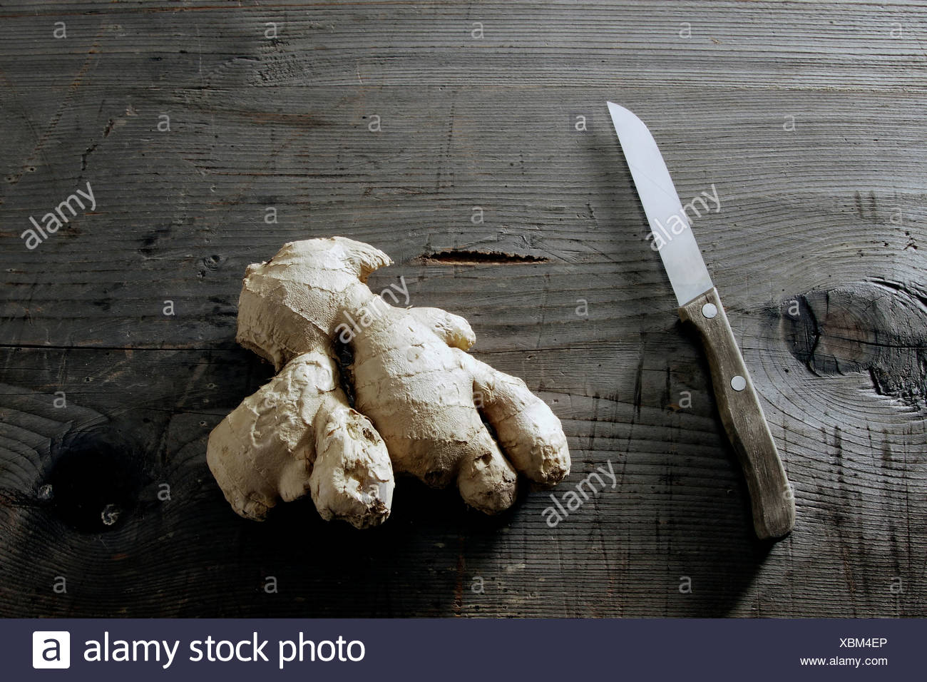 Ginger (Zingiber officinale) rhizome on a rustic wooden surface - Stock Image