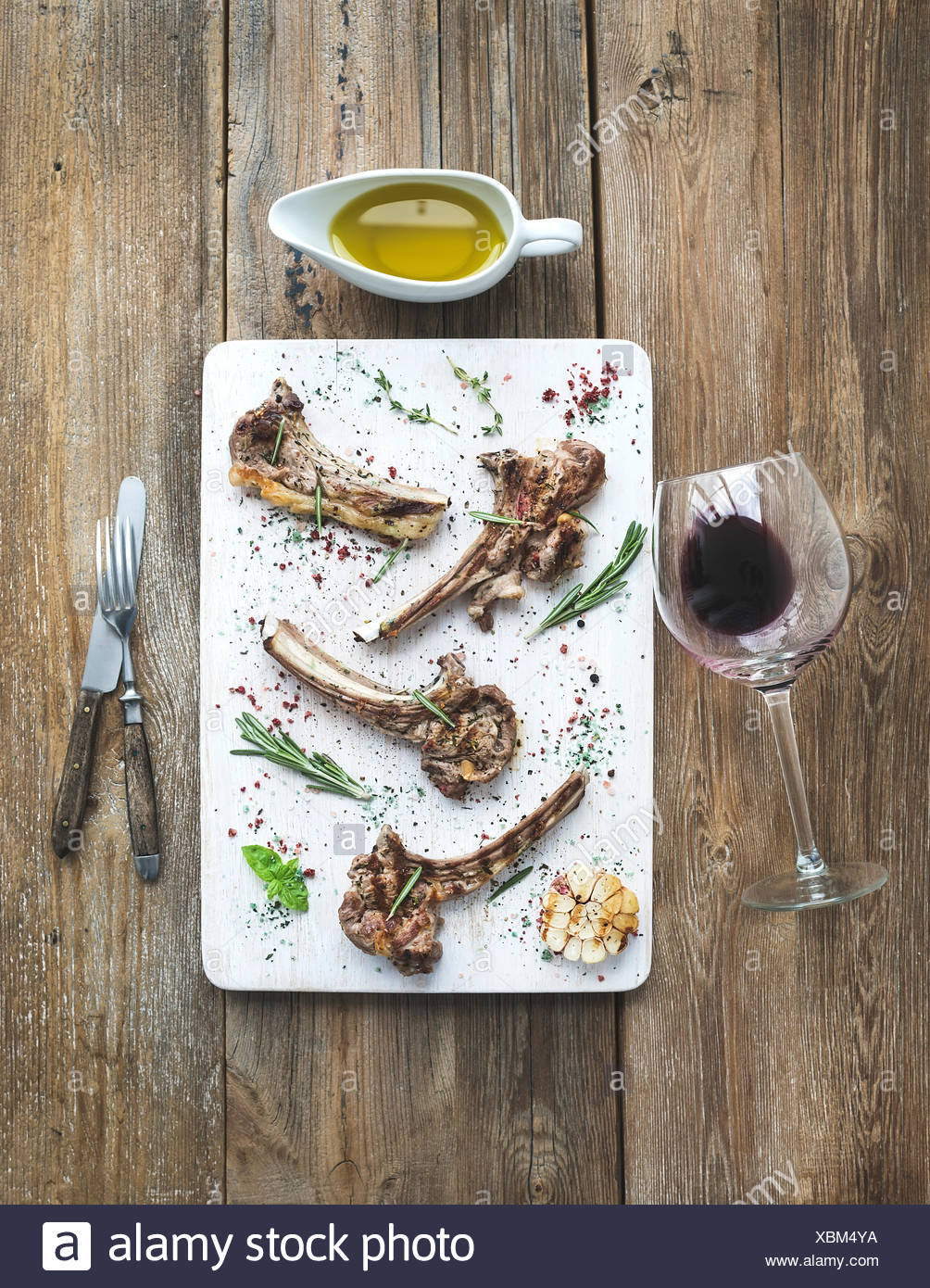 Grilled lamb chops. Rack of Lamb with garlic, rosemary and spices on white serving board, wine glass, oil in a saucer, dinnerwar - Stock Image