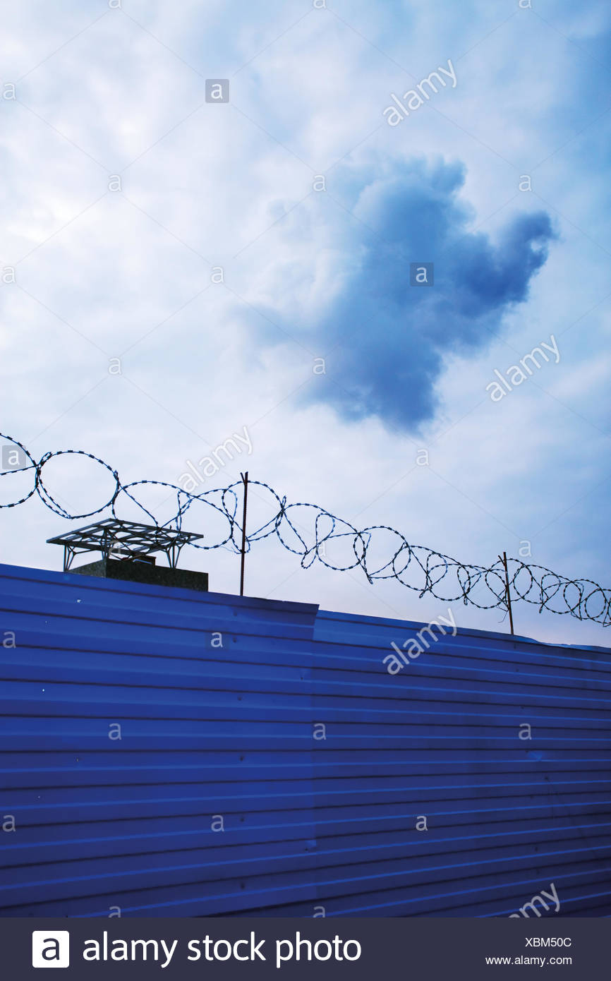 Cloud above razor wire fence - Stock Image