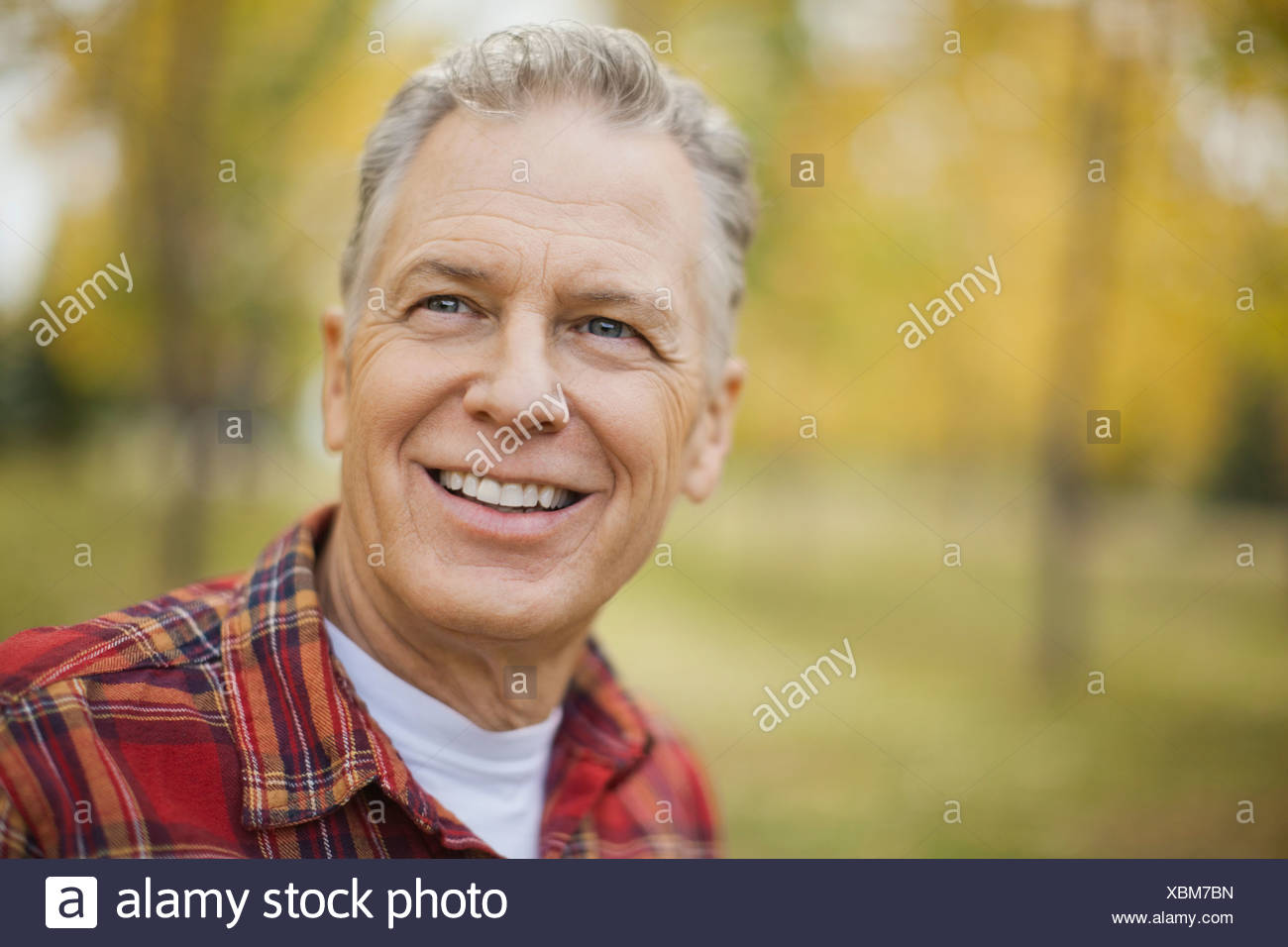 Happy mature man looking away at park - Stock Image