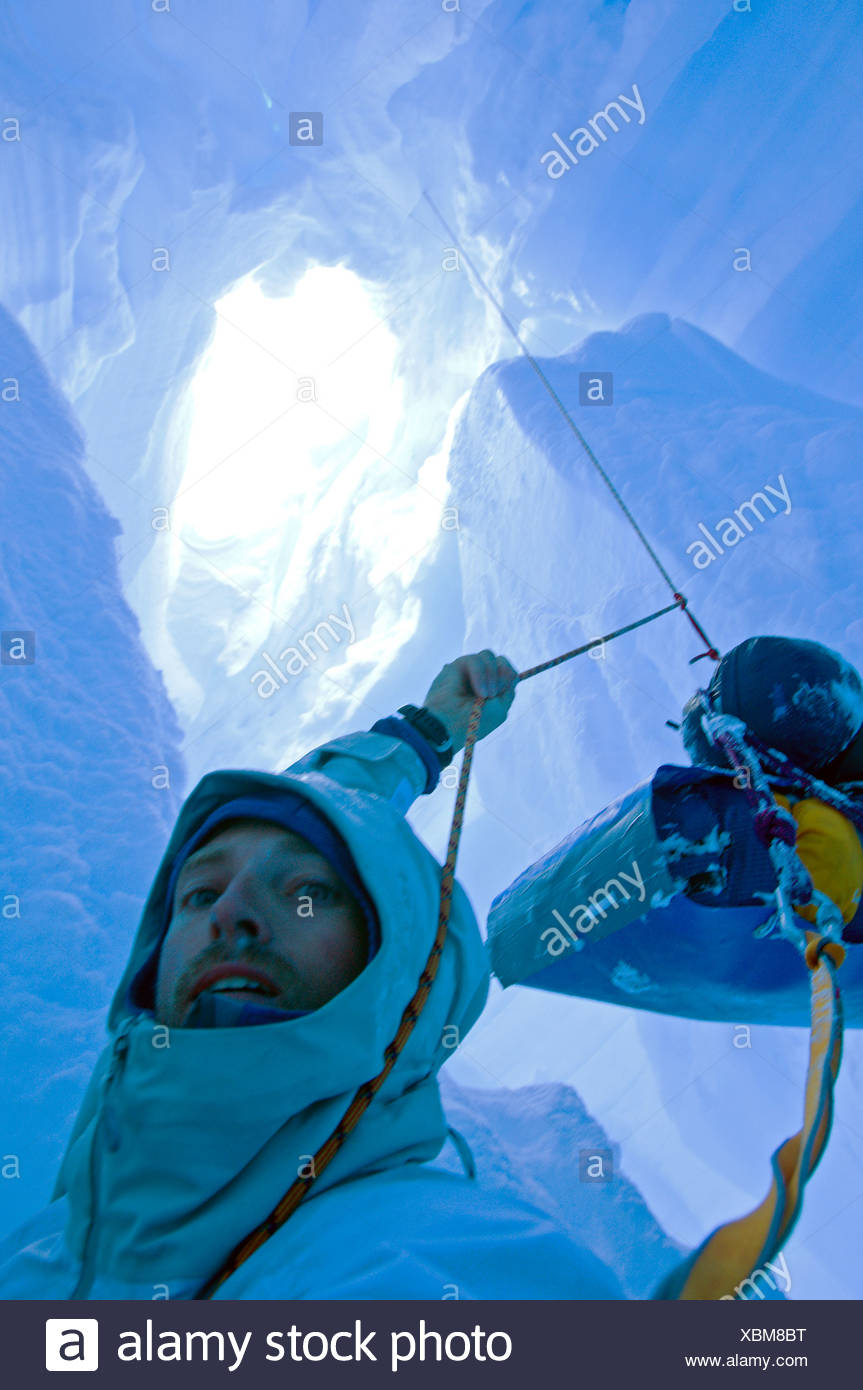A skier who fell down a crevasse while travelling on a glacier in the Darwin Range, Chile, is in a tricky situation Stock Photo