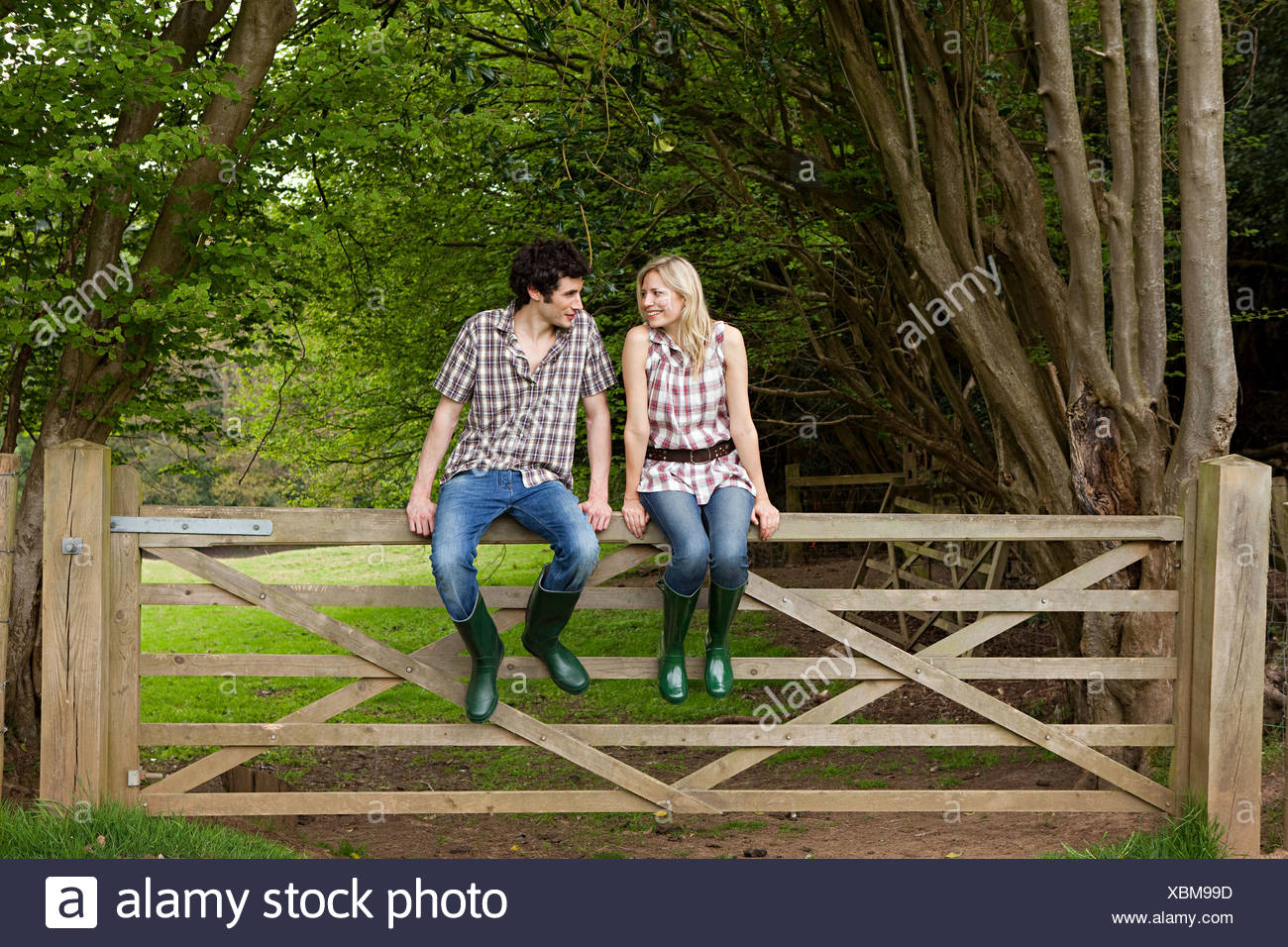 Young couple sitting on gate - Stock Image