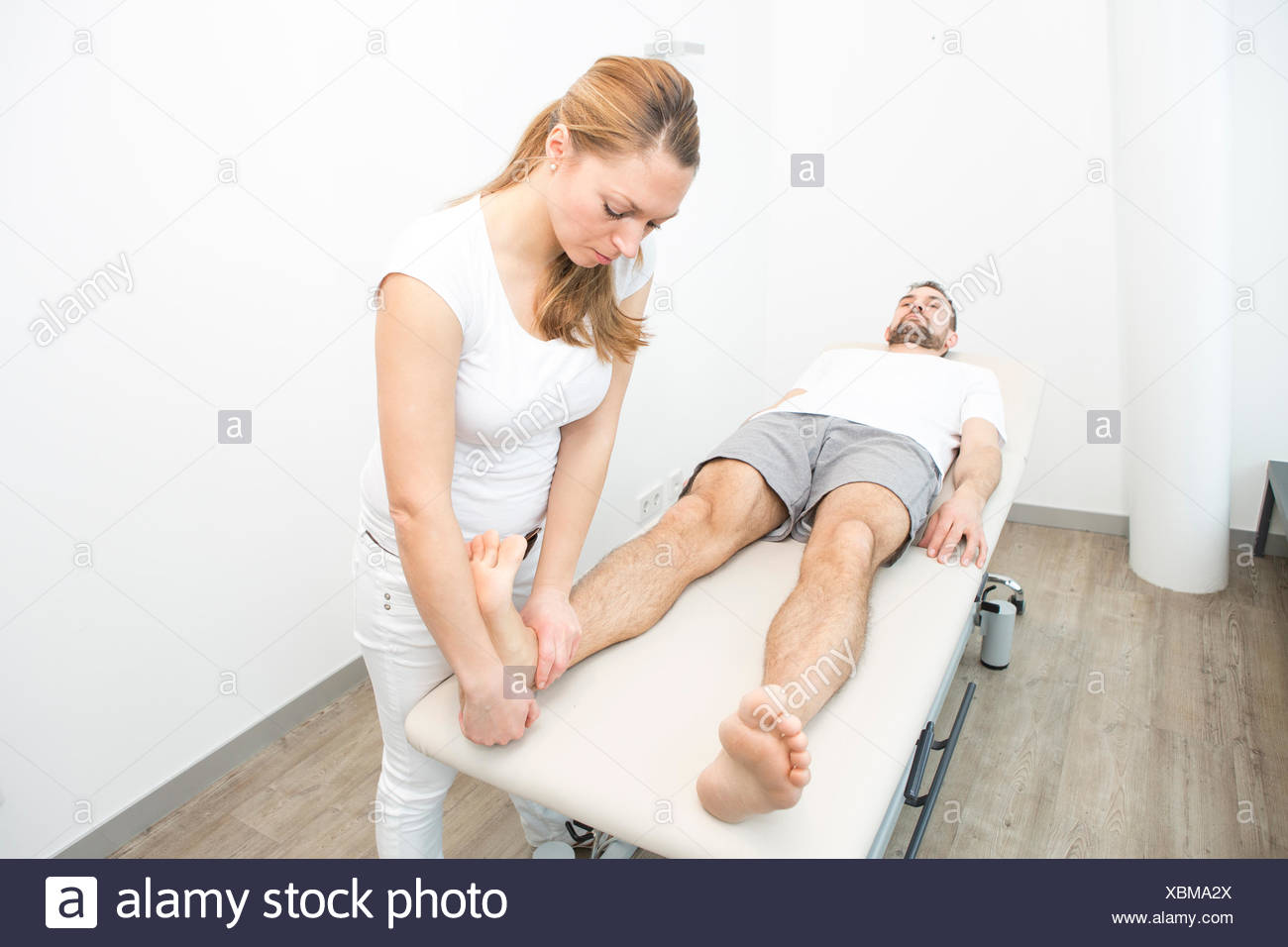 Physiotherapist helping patient to do leg exercise - Stock Image