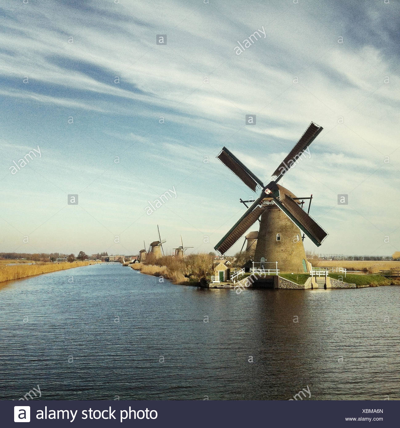 Windmill by river - Stock Image