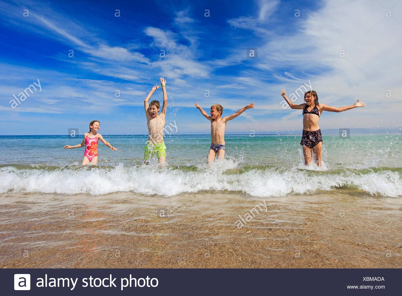 4, activity, swimming trunks, swim suit, joy, sky, hands, youngsters, boy, children, boy, coast, sea, girl, fun, joke, play, spor - Stock Image