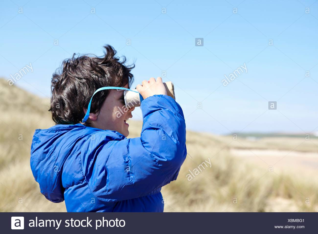 Young boy on beach, looking through pretend binoculars - Stock Image