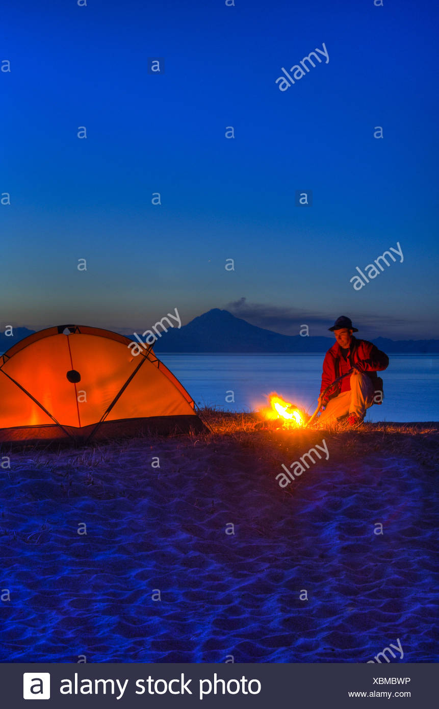 Man sitting at campfire with Cook Inlet and Mt. Redoubt in the background, Kenai Peninsula, Southcentral Alaska, Spring Stock Photo