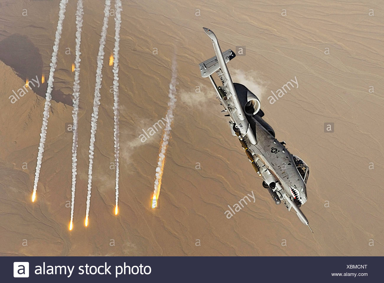 An A-10 Thunderbolt II deploys flairs over Afghanistan. A-10s provide close-air support ground troops in Afghanistan Iraq. - Stock Image