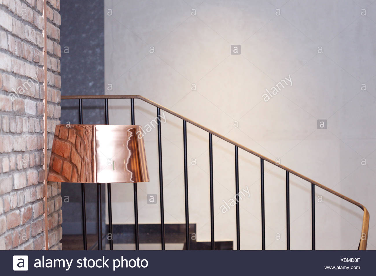 Brass floor lamp next to a brick wall near stairs stock image