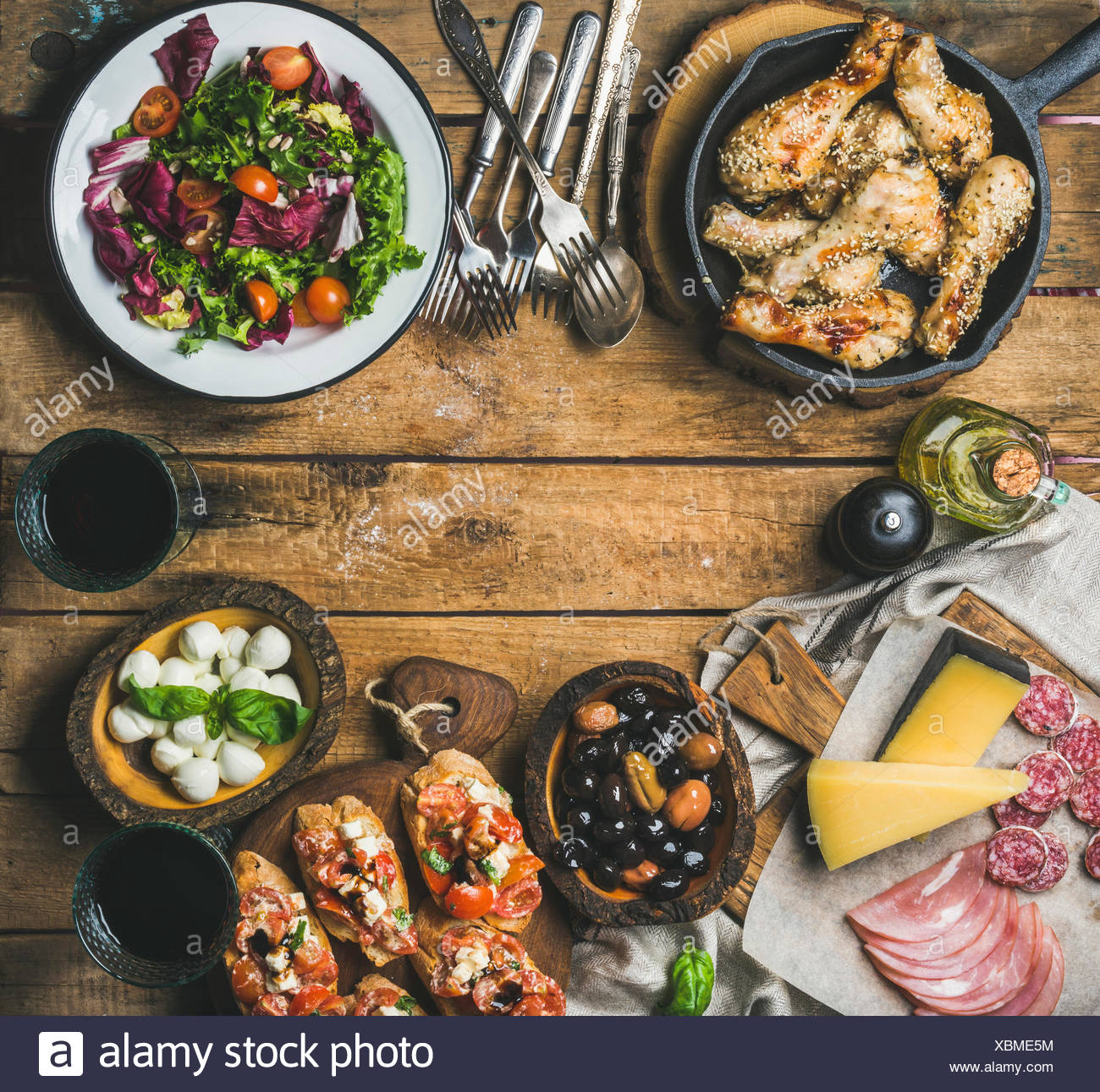 Party table arrangement. Rustic table set with vegetable salad, olives, chicken, tomato and feta cheese brushettas or sandwiches, various snacks and r - Stock Image