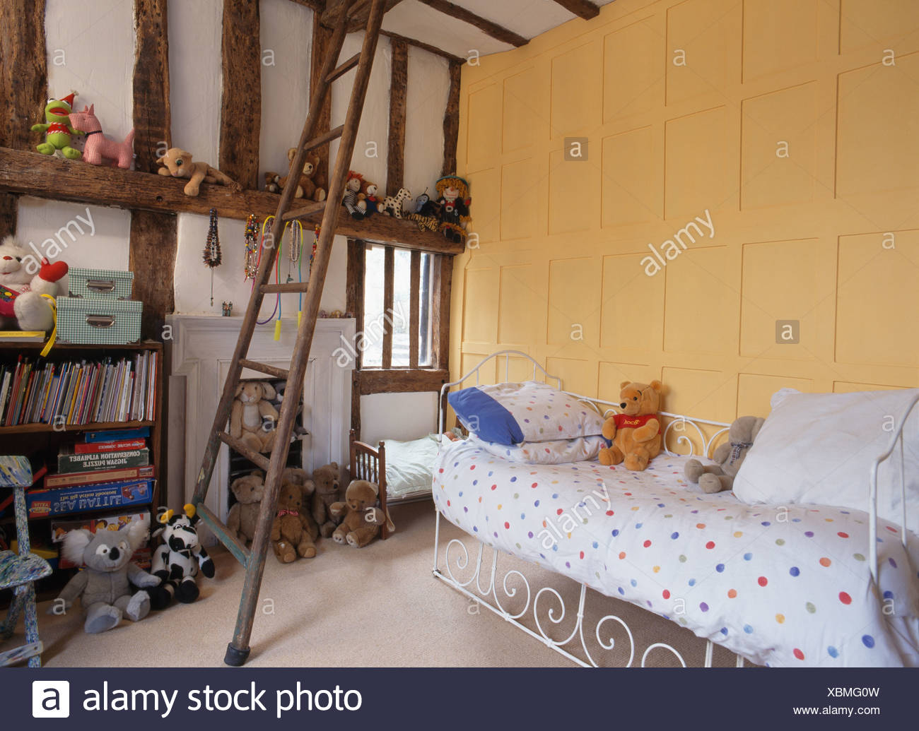 Paneled Yellow Wall Above White Wrought Iron Bed In Child S Bedroom With Wooden Ladder Stock Photo Alamy