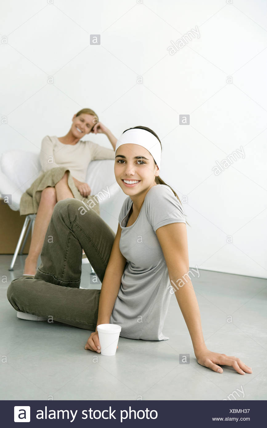 Teen girl sitting on the ground with drink, smiling at camera, mother sitting in background - Stock Image