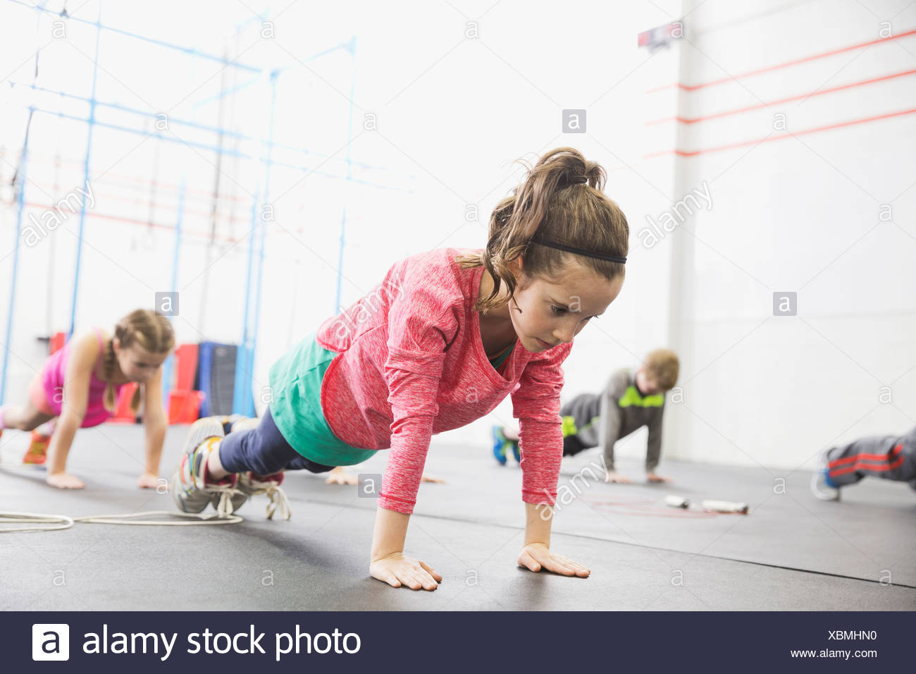 Determined girl practicing plank-holds - Stock Image
