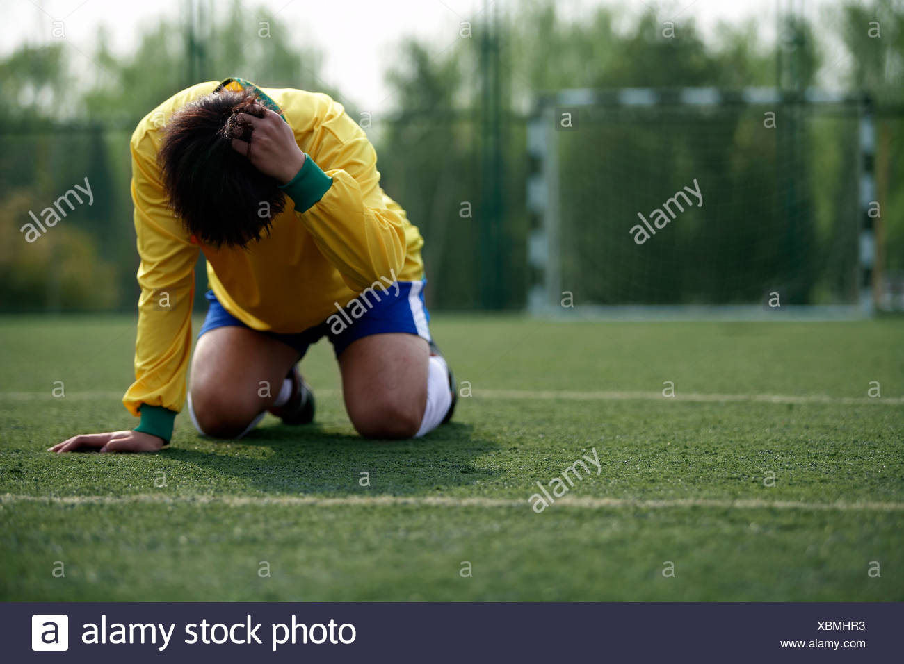 Disappointed Soccer Player On His Knees - Stock Image