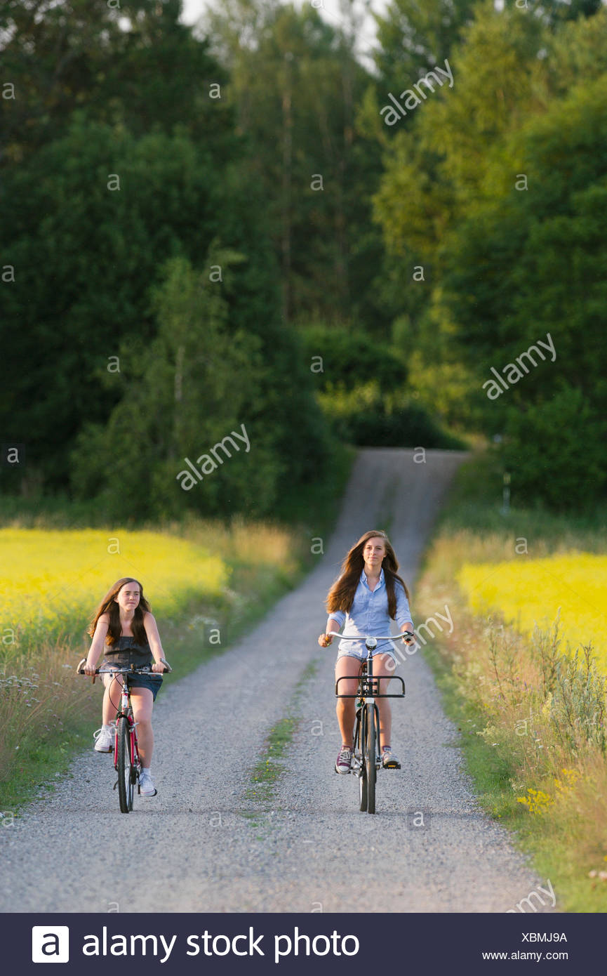 Sweden, Sodermanland, Stigtomta, Teenage girl (14-15) with her younger friend (10-11) cycling on rural road - Stock Image