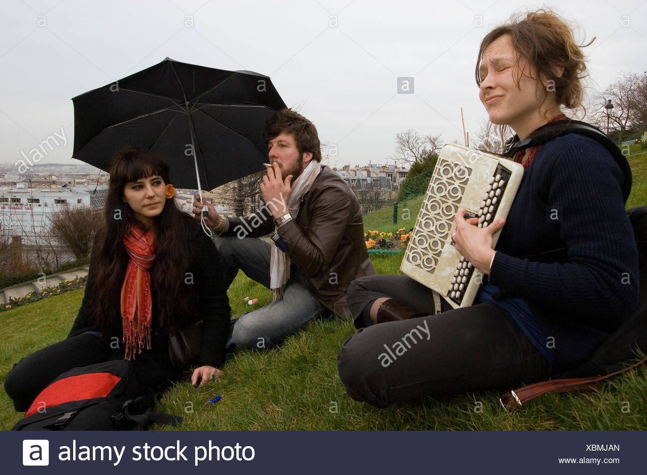 Friends meet on a lawn below Sacre Coeur. - Stock Image
