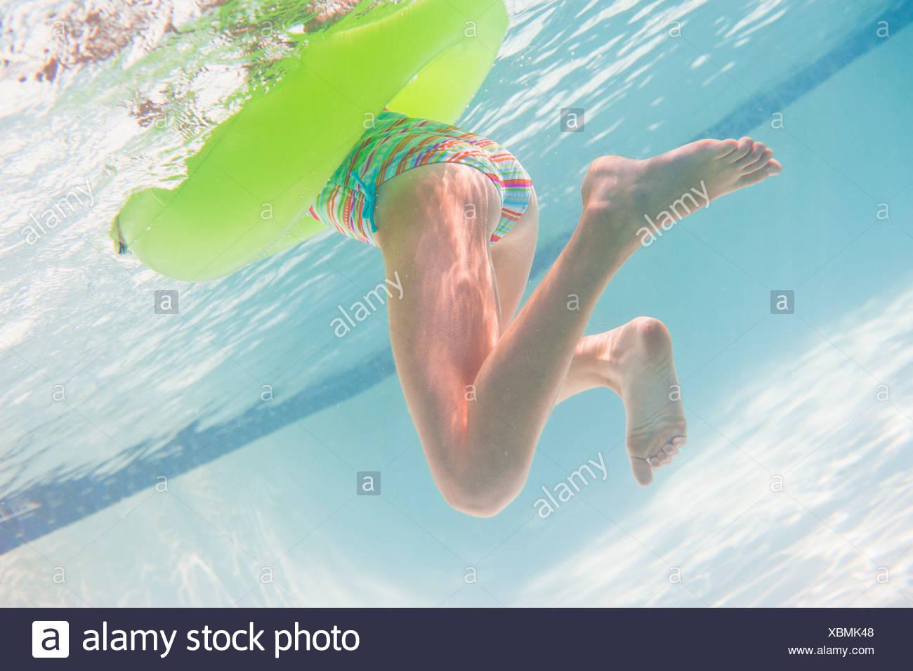 USA, New York State, Old Westbury, Girl swimming underwater - Stock Image