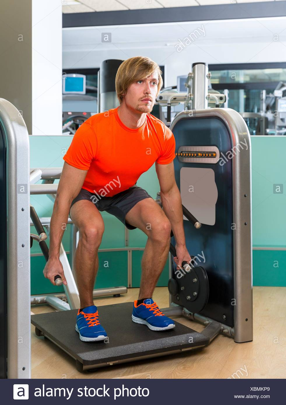 Gym squat machine exercise workout blond man at indoor. - Stock Image
