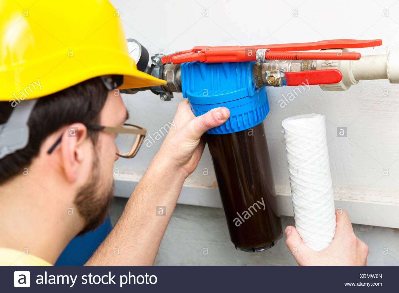 water filtration - plumber changing dirty water filter - Stock Image