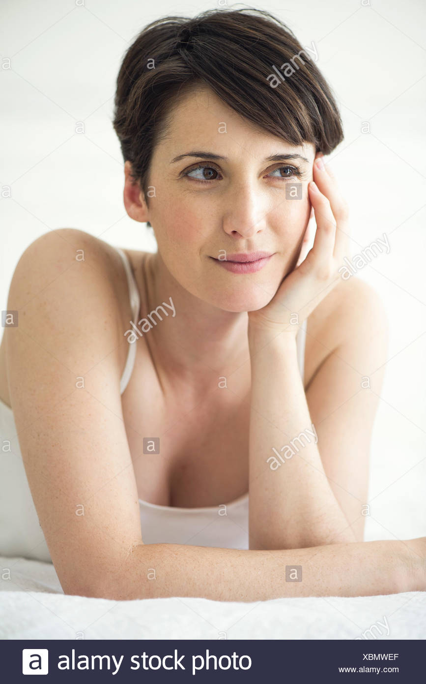 Woman lying on bed, portrait - Stock Image