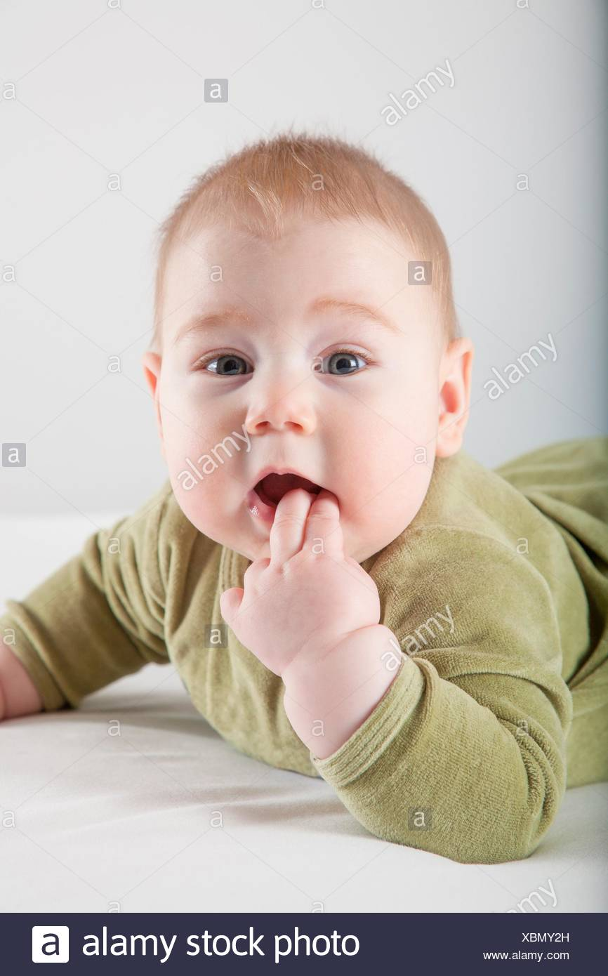 six months age blonde baby green velvet onesie lying on white sheet bed smiling happy face. Stock Photo
