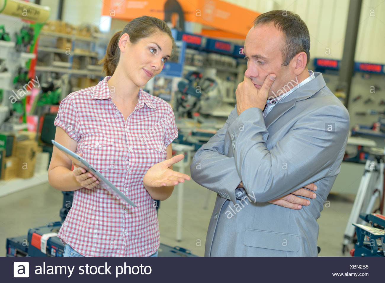 Lady holding tablet, trying to persuade man - Stock Image