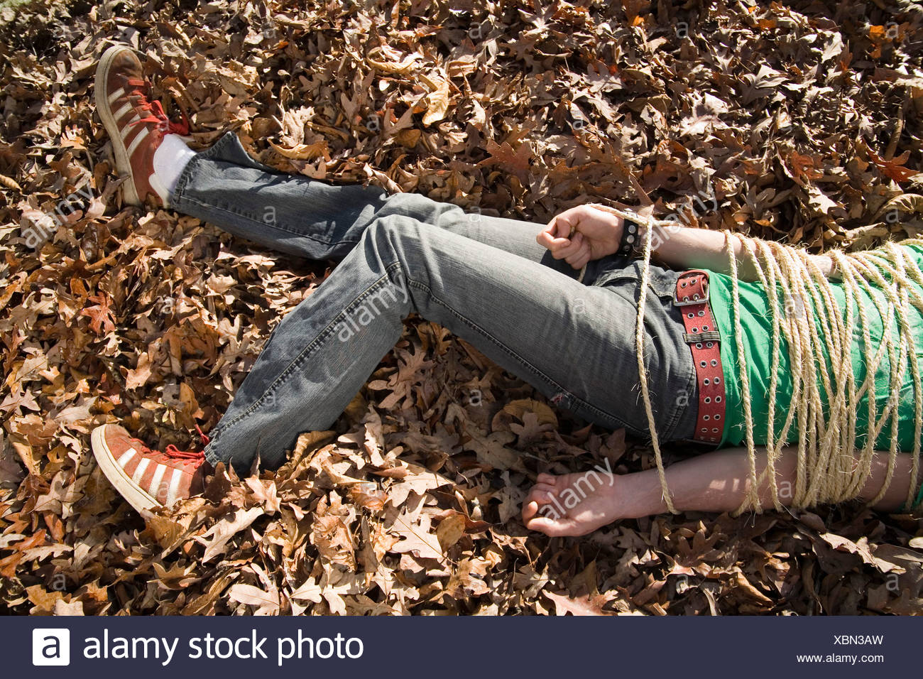 Man lying in a pile of autumn leaves bound in rope - Stock Image