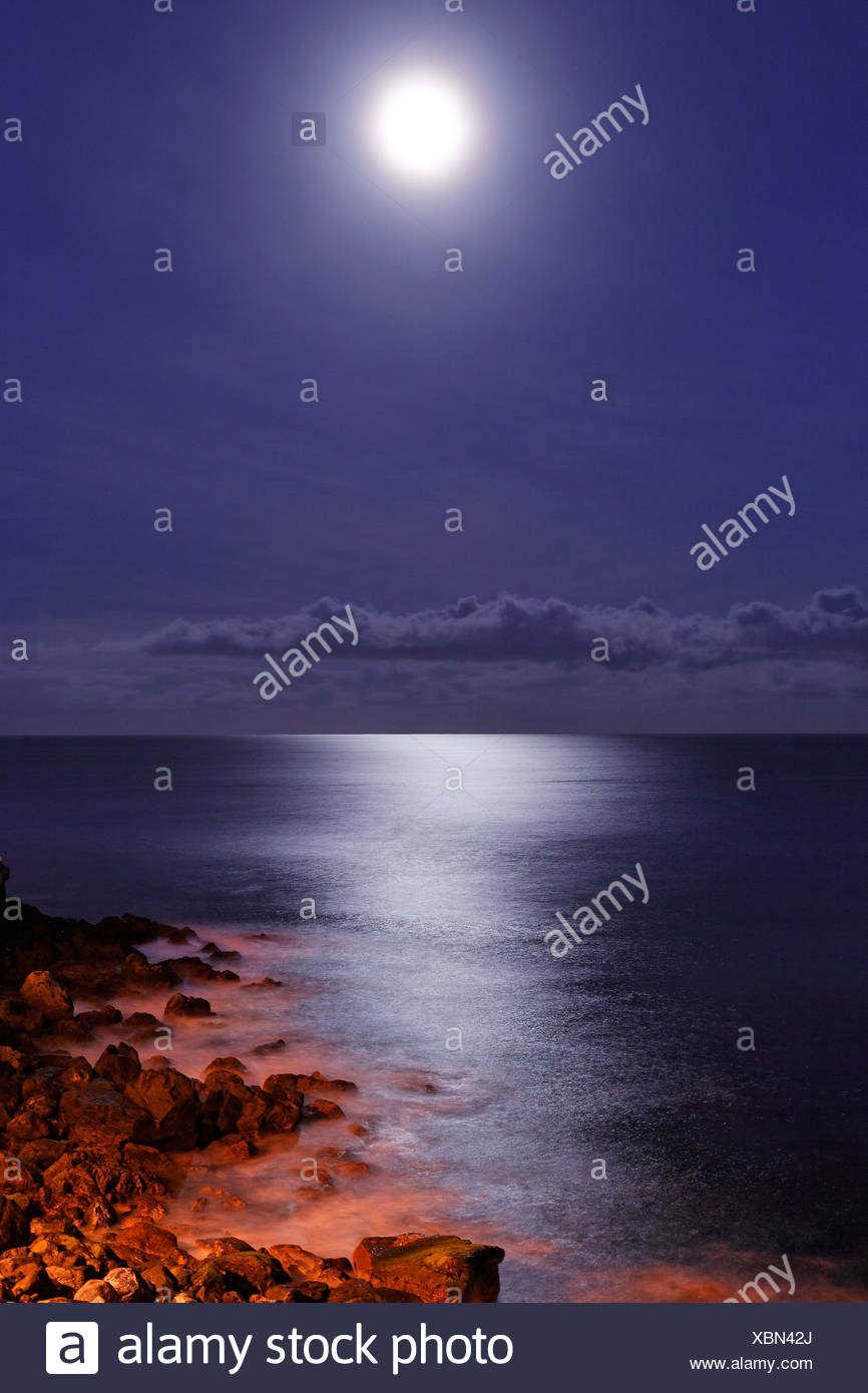 Sea and the rocky coast in the moonshine, Camara de Lobos, Madeira, Portugal - Stock Image