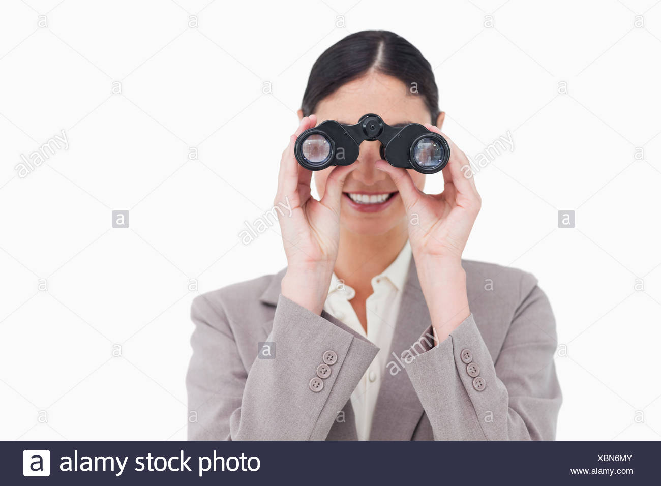 Smiling businesswoman looking through spy glasses - Stock Image