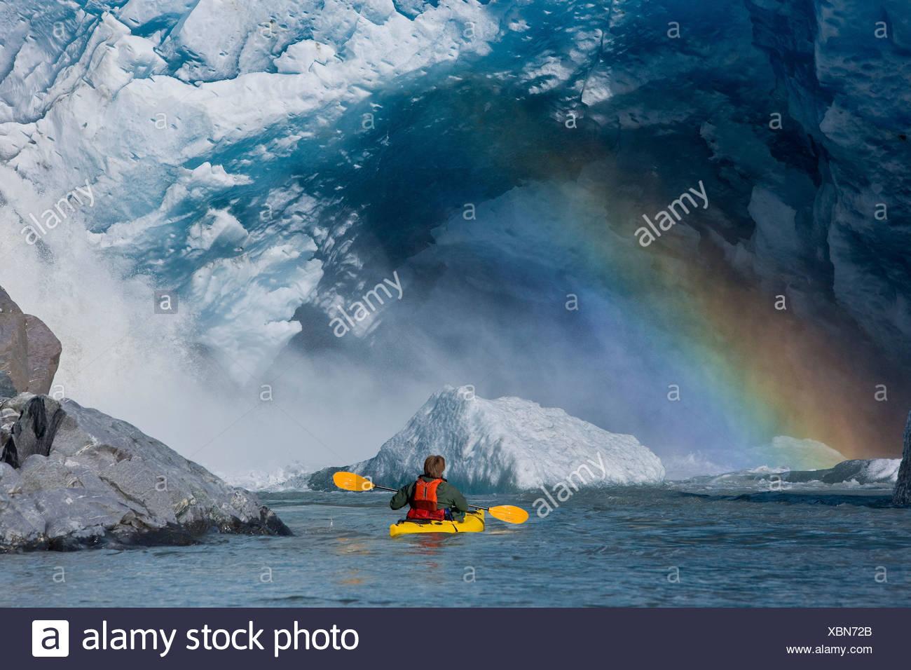 A kayaker explores a melt stream gushing from beneath Mendenhall Glacier, Mendenhall Lake, Tongass National Forest, Alaska - Stock Image