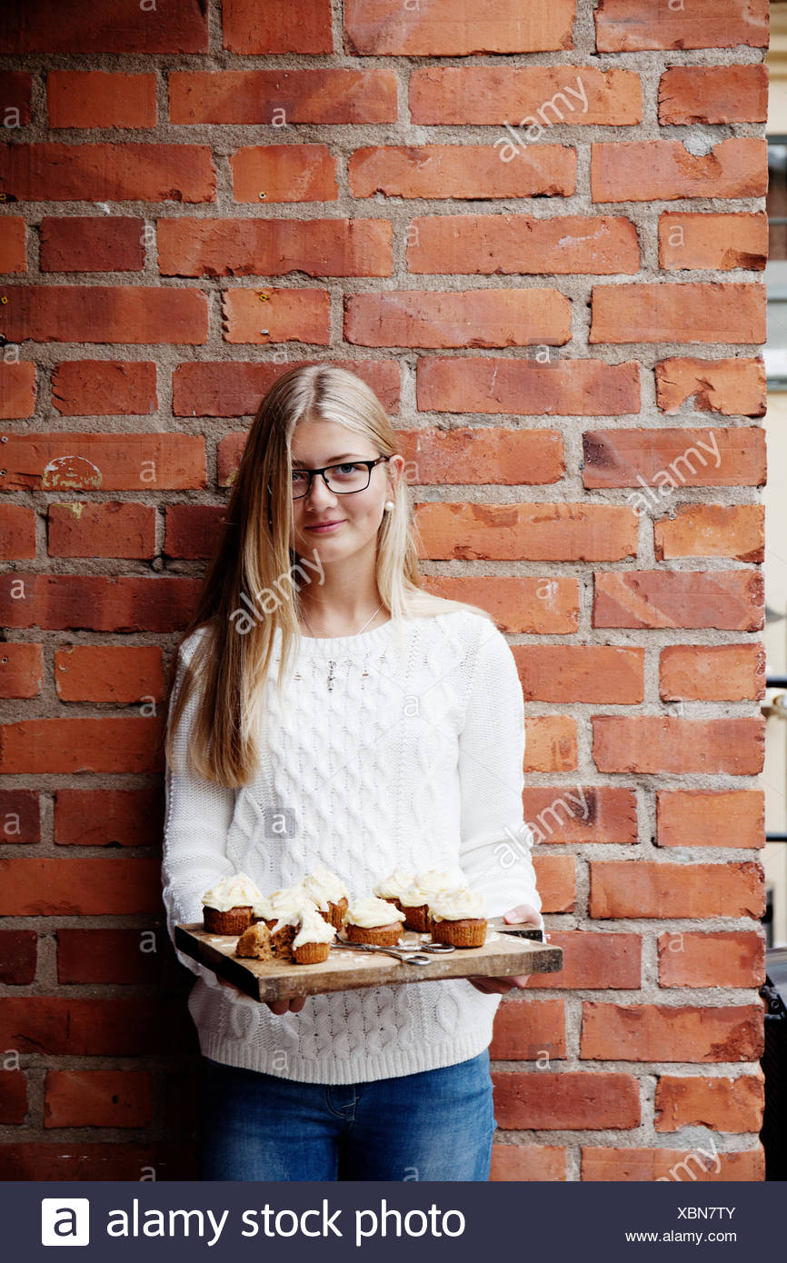 Sweden, Uppland, girl (14-15) with cupcakes against brick wall - Stock Image