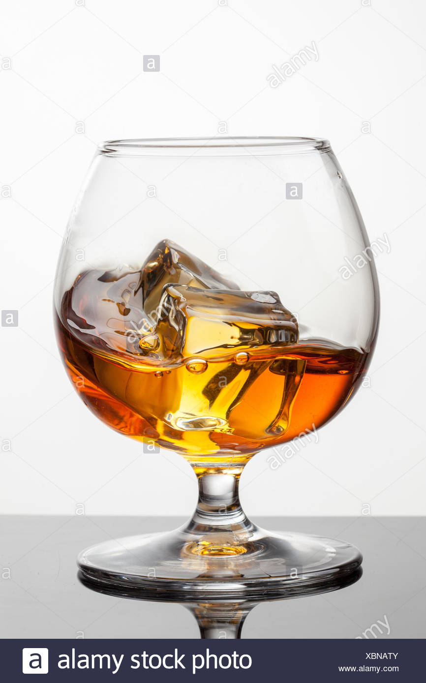 Splash of whiskey with ice in glass isolated on white background. Raw photo Stock Photo