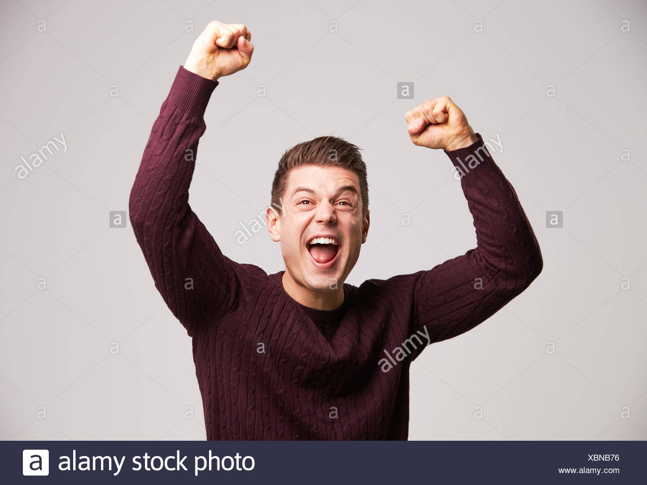 Portrait of a celebrating young white man punching the air - Stock Image