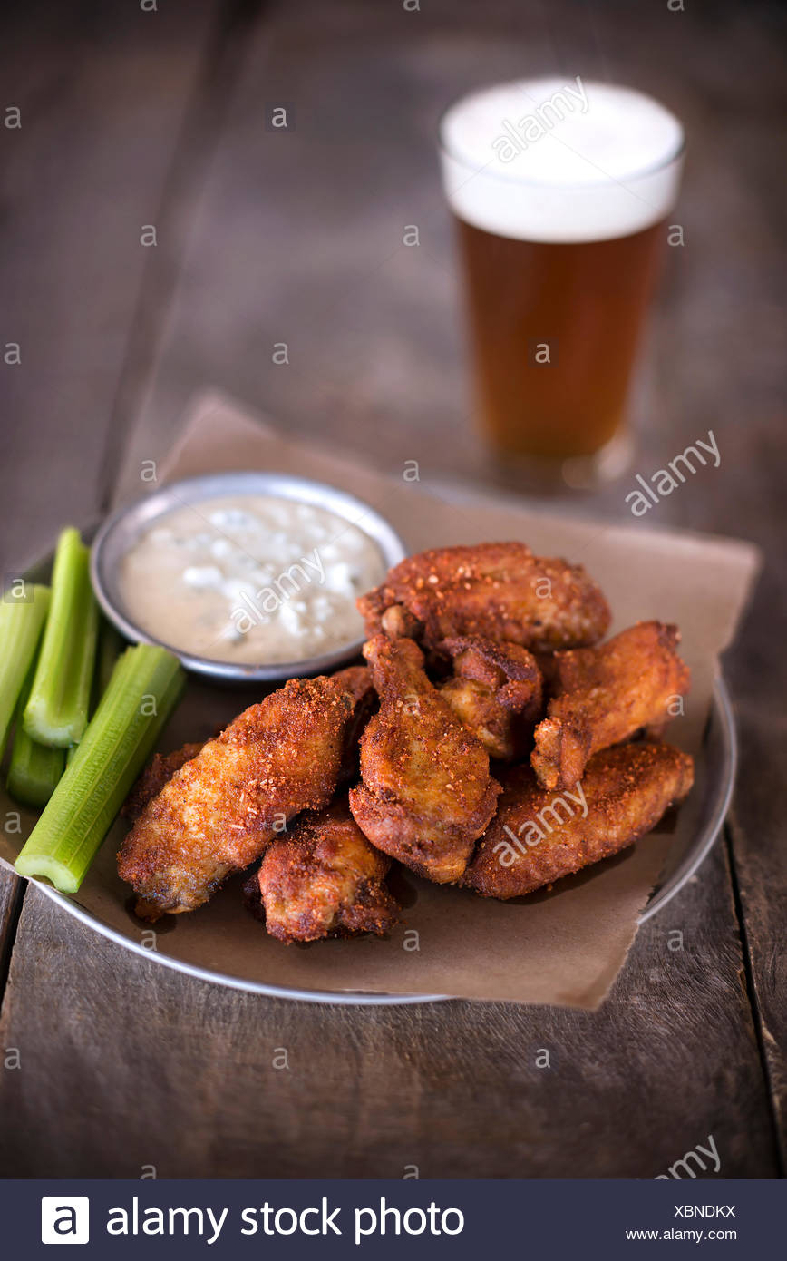 Tray of dry rub wings with celery, blue cheese and a pint of beer on a rustic wood surface. - Stock Image