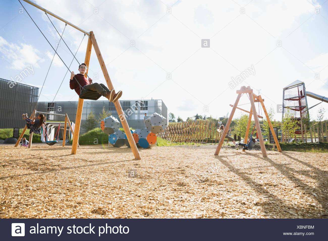 Boy swinging at sunny playground - Stock Image