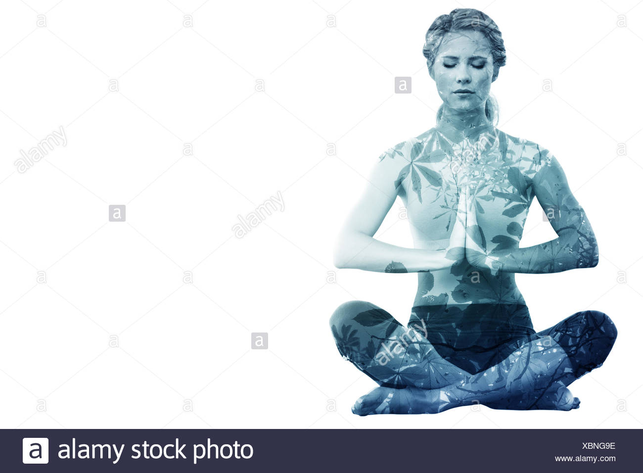 Composite image of calm blonde sitting in lotus pose with hands together - Stock Image