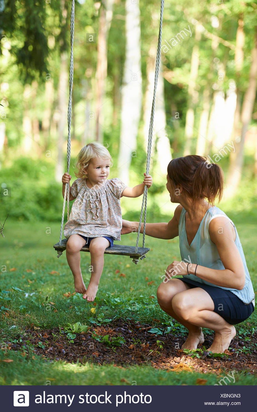 Mid adult mother and toddler daughter playing on garden swing - Stock Image