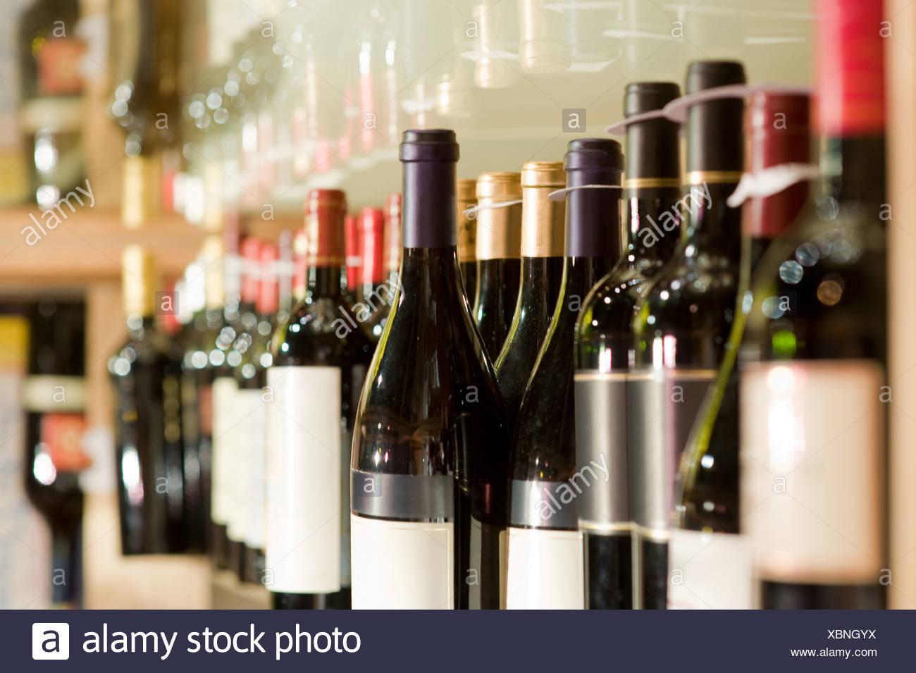 A selection of wine bottles on a shelf - Stock Image