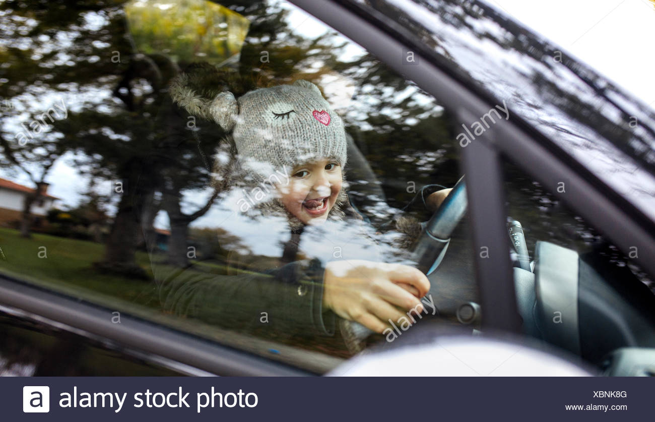 Portrait of happy little girl sitting on her mother's lap while driving car Stock Photo