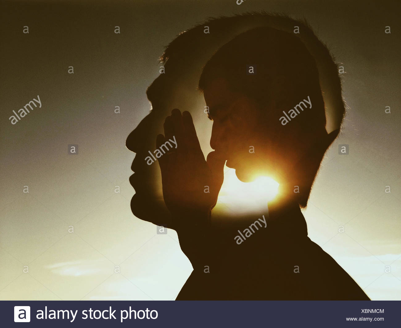 Digital composite of man praying - Stock Image