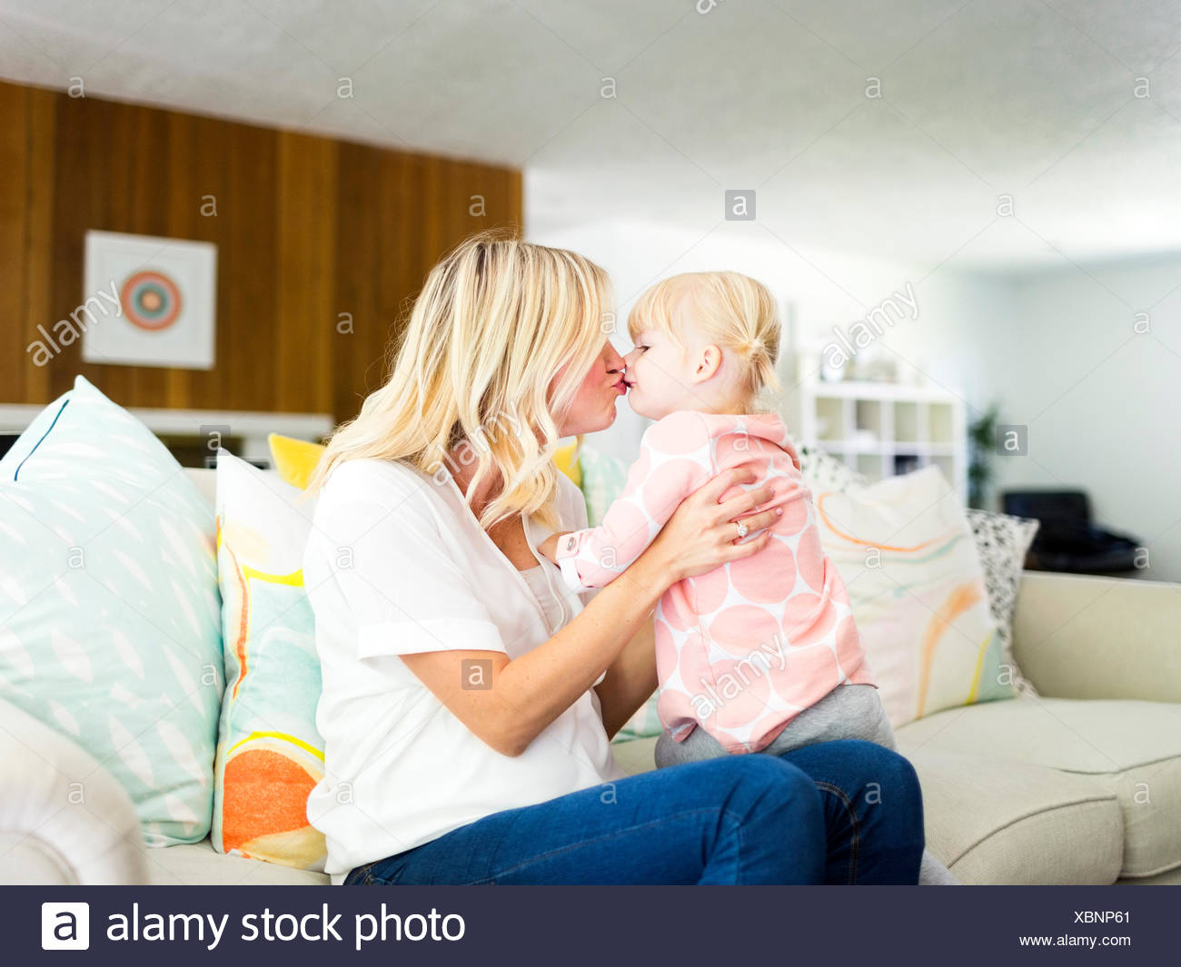 Woman kissing daughter (2-3) in living room Stock Photo
