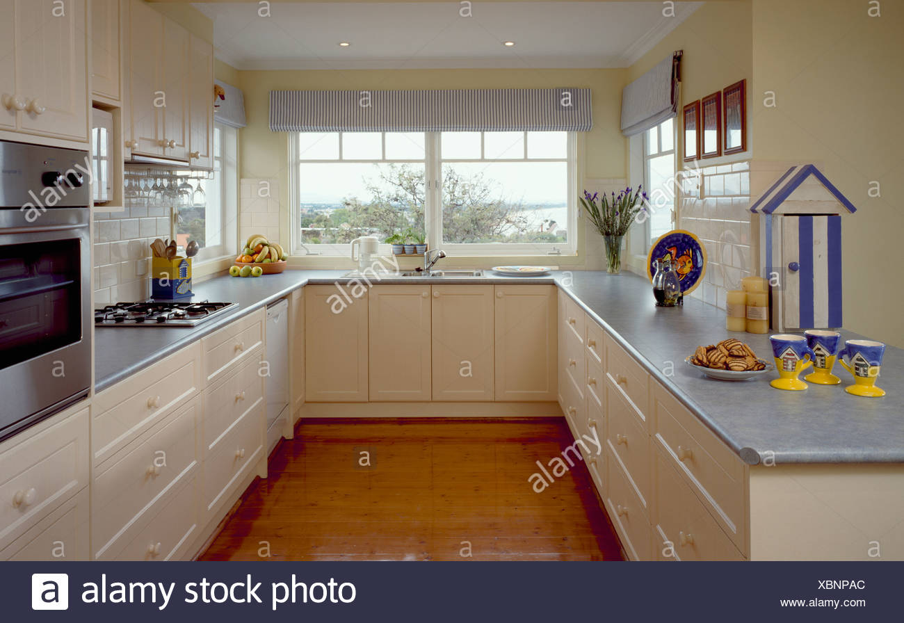 Yellow and blue cups on grey worktop on cream units in modern kitchen with wooden flooring and grey blinds on the windows