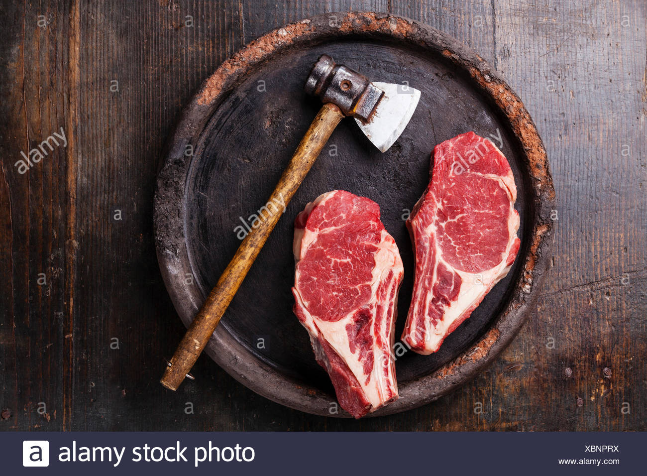 Heart shape Raw meat Ribeye steak entrecote and meat cleaver on dark background - Stock Image