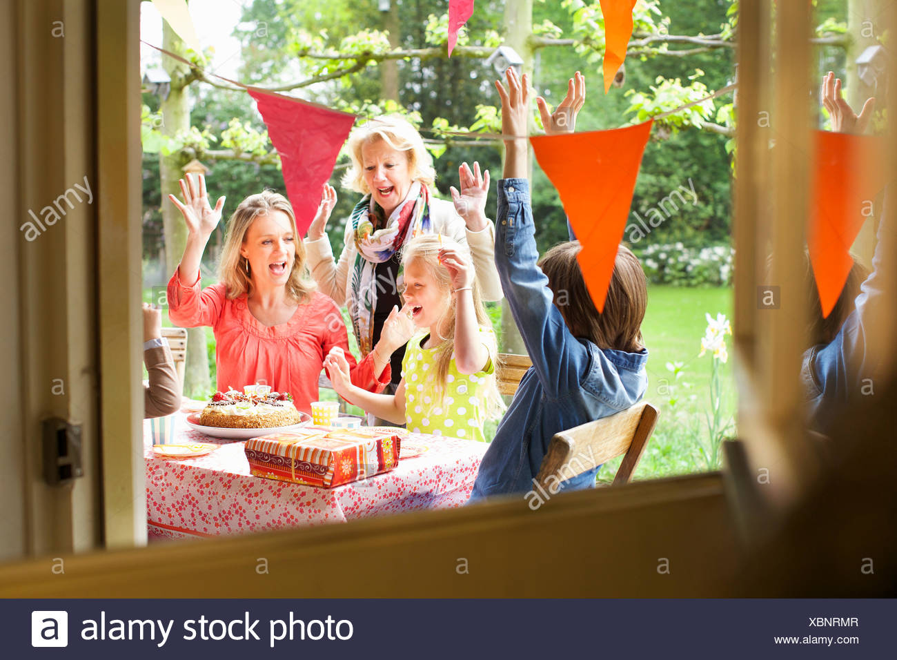 Family singing and cheering at birthday party - Stock Image