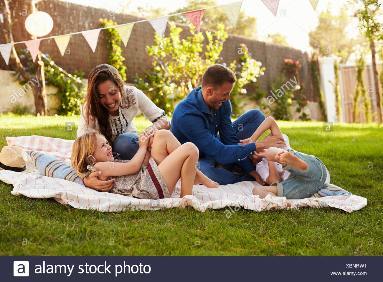 Parents Playing Game With Children On Blanket In Garden - Stock Image