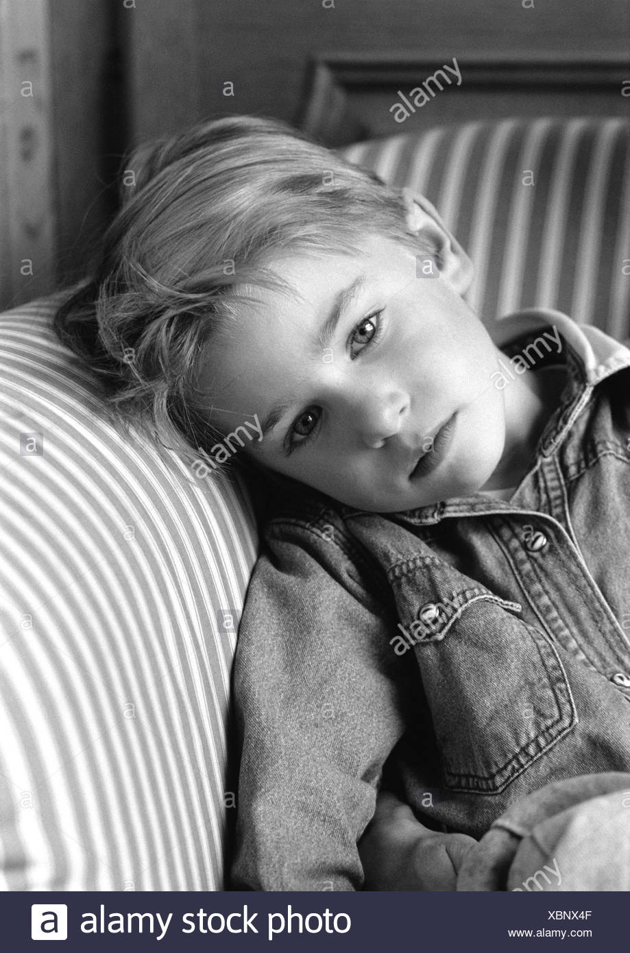 Young boy leaning head on chair arm, black and white portrait. - Stock Image