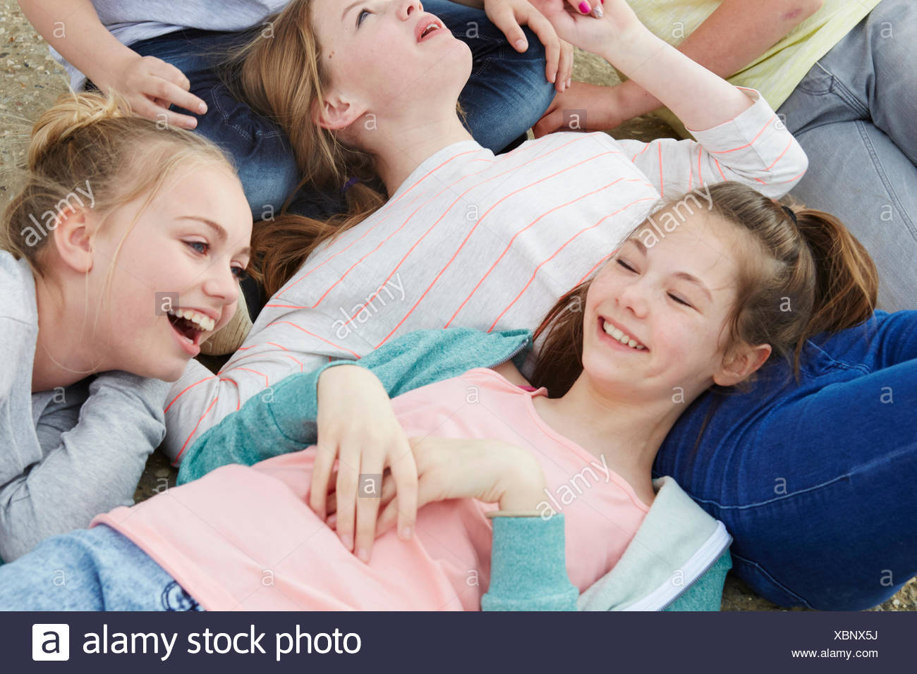 Cropped view of five boys and girls lying on ground - Stock Image