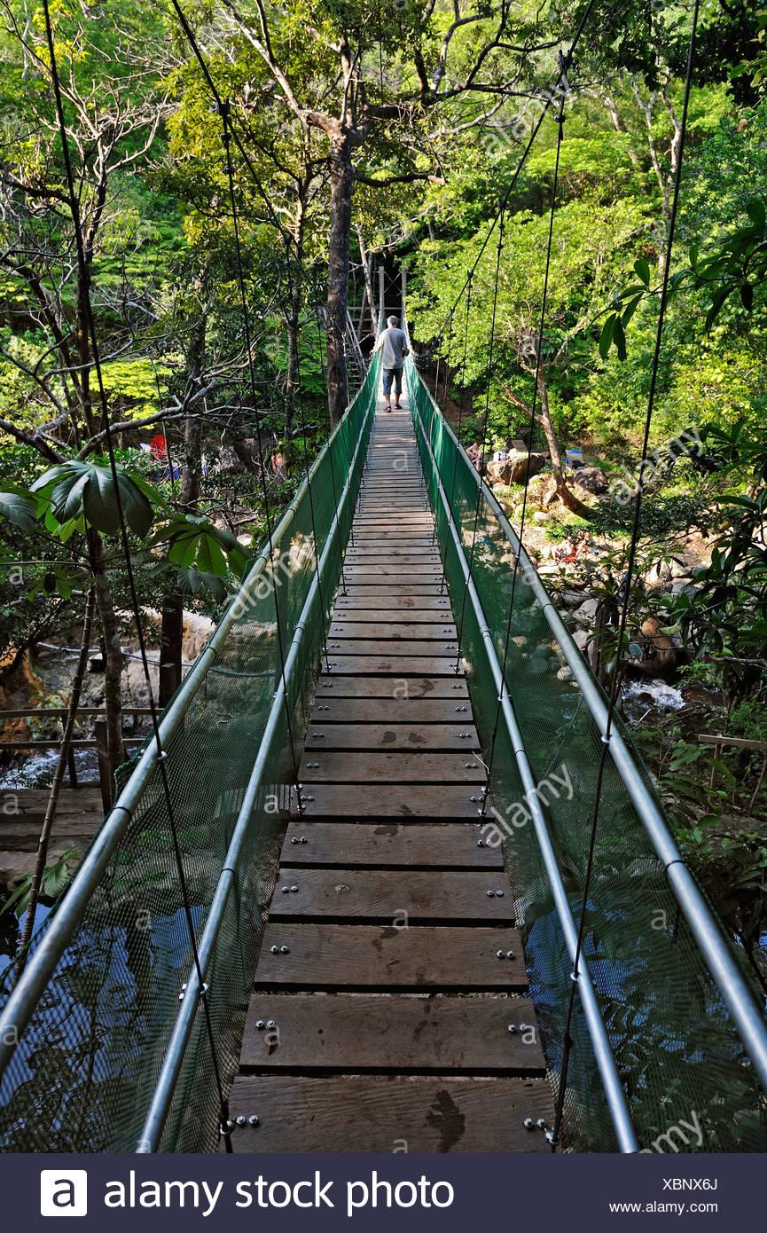 Suspension bridge leading to the hot springs near the Hacienda Guachipelin, near Liberia, Guanacaste province, Costa Rica - Stock Image