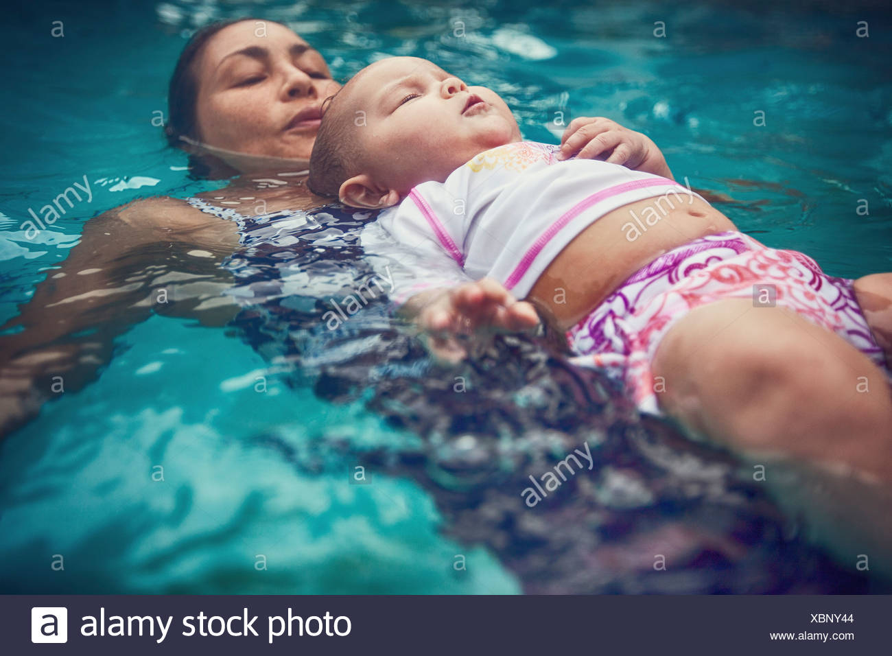 Mother and baby daughter floating on backs in water - Stock Image