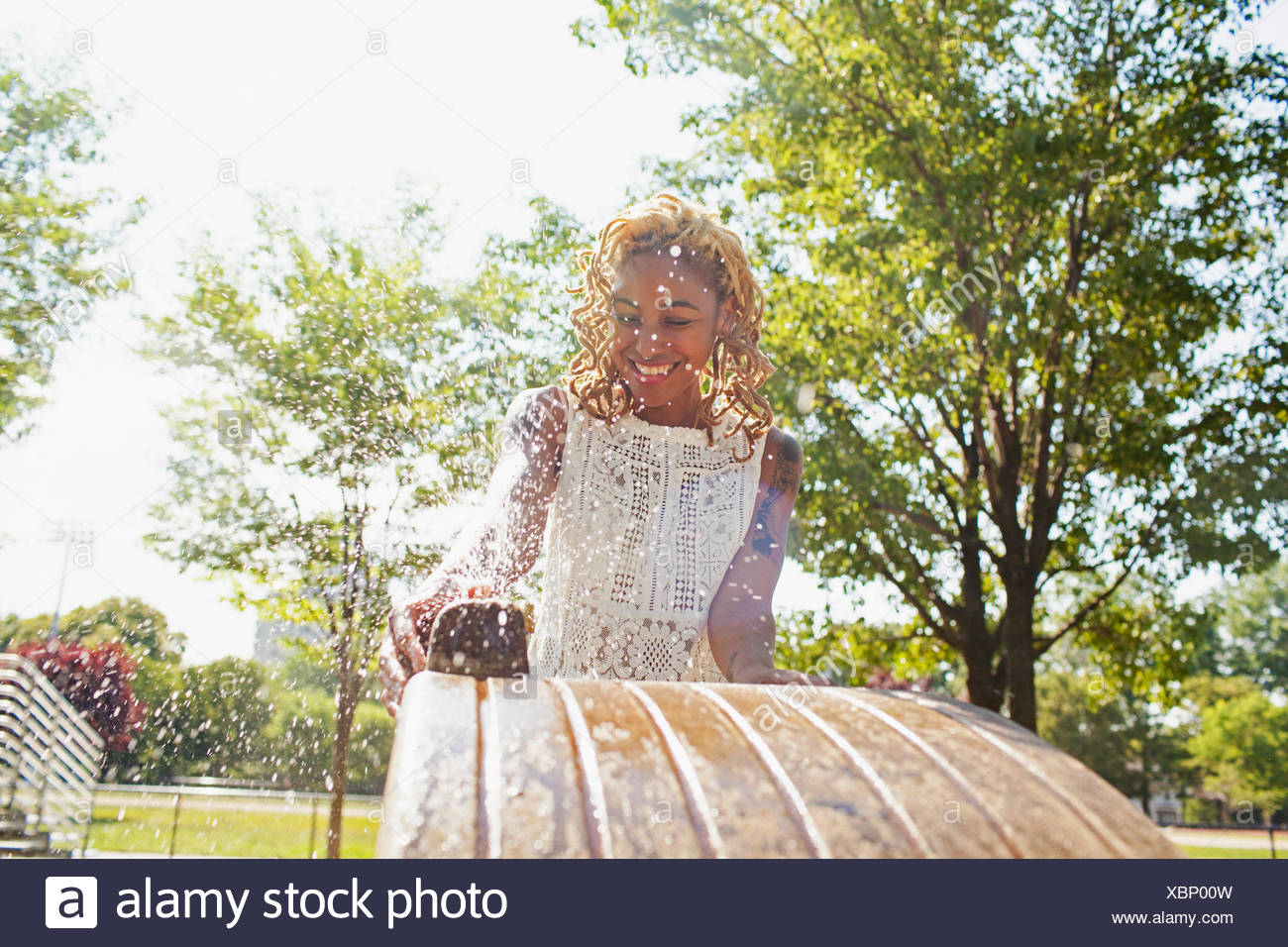 A young woman at a water fountain - Stock Image